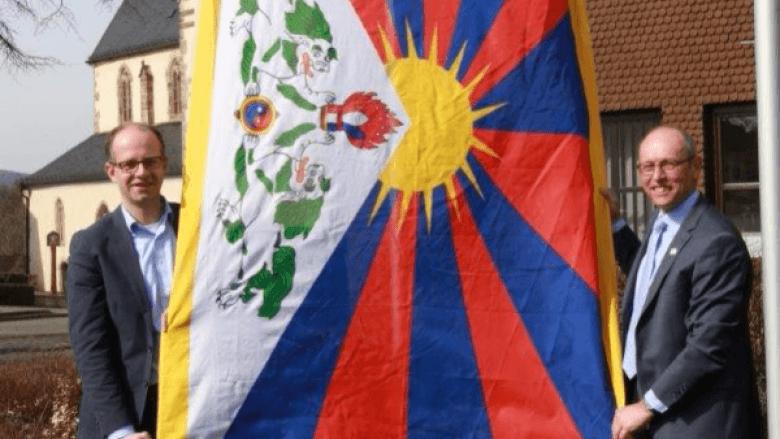 Michael Brand MdB (links) und Bürgermeister Jürgen Hahn hissen vor dem Rasdorfer Rathaus die Tibet-Flagge.