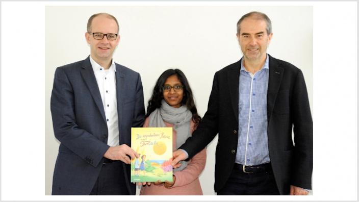 """Das 1. Exemplar """"Die wunderbare Reise nach Farbula"""" überreichten die Autorin Teresa George (Mitte) und Dr. Wolfram Geiger (rechts), Vorsitzende des Fördervereins Jollydent e.V., an Fulda-MdB Michael Brand und Vater von 3 Kindern"""